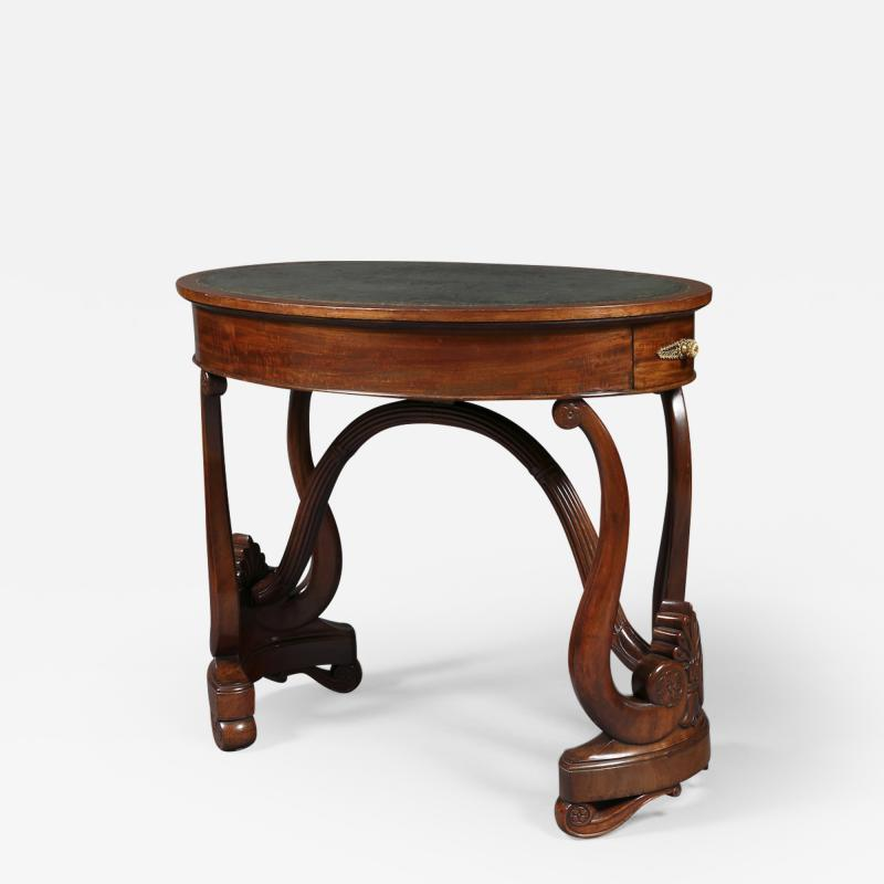 A Charles X Carved Mahogany Oval Writing Table of Unusual Form