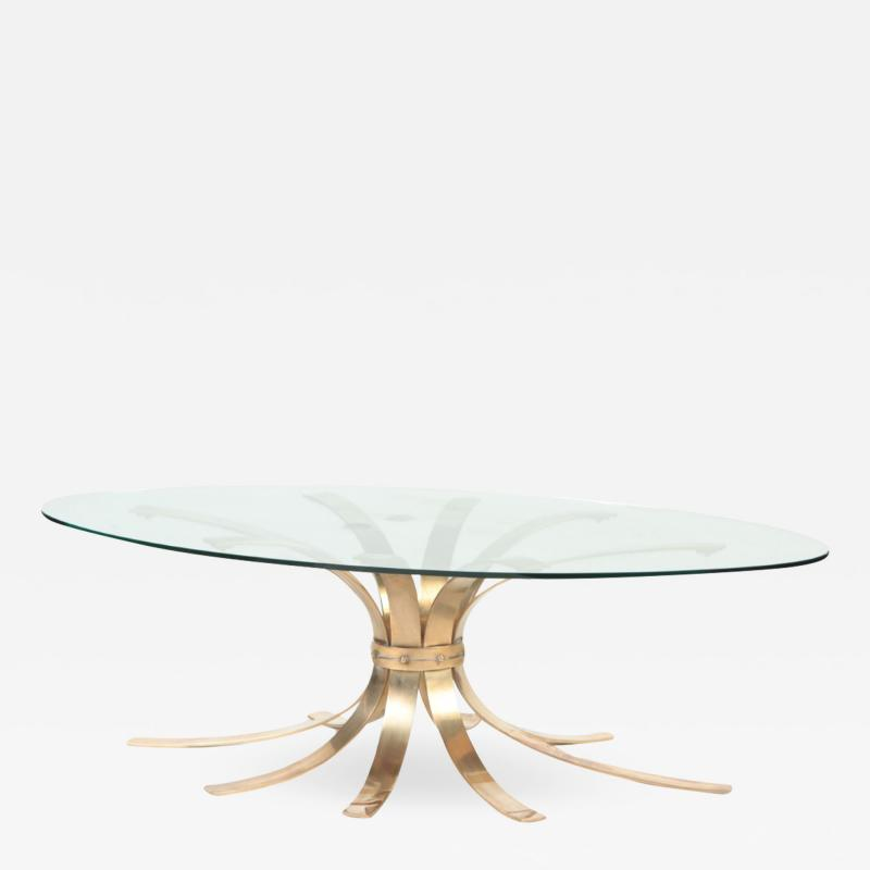 A Mid Century Modern oval bronze coffee table with a glass top France C 1960