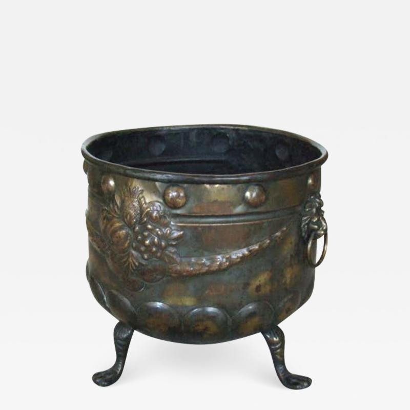 A Patinated Brass Repousee Firewood Vessel