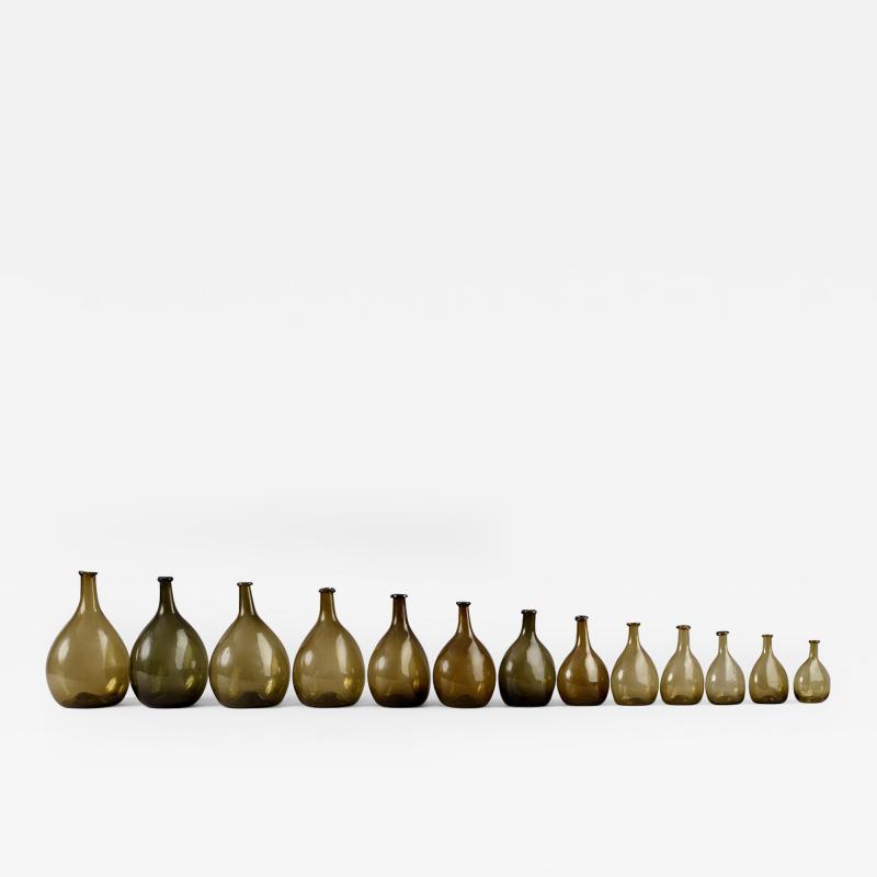 An Exceptional Set of 13 Graduated Blown Chestnut Bottles