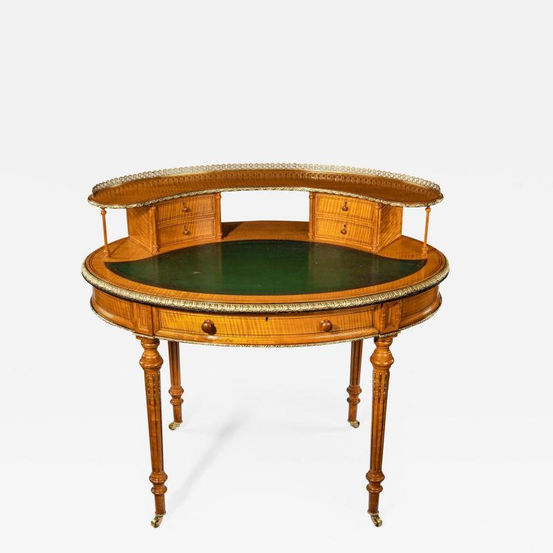 An unusual Victorian freestanding oval satinwood desk