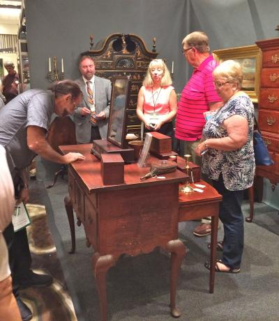 Potential buyers examine a dressing table in Gary Yeaton