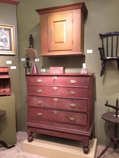 Sold! The hanging cupboard and early ball-foot chest. Booth of Elliott & Grace Snyder.
