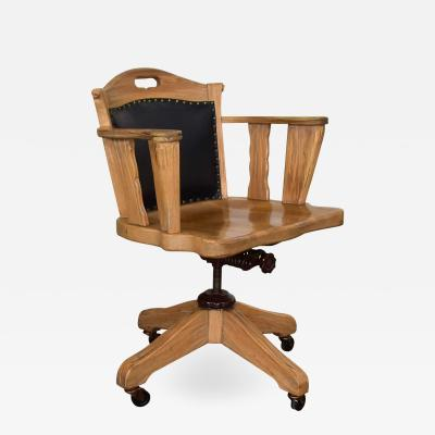 A Brandt Ranch Oak Furniture Vintage ranch oak rolling desk chair with leather back by a brandt company