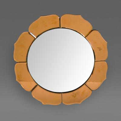 A French art deco convex mirror surrounded by peach colored petals