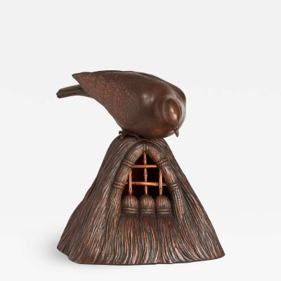 A JAPANESE CARVED WOOD OKIMONO OF A DOVE PEERING INTO A GRAIN STORE