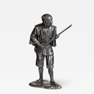A Meiji period bronze of a huntsman carrying a gun