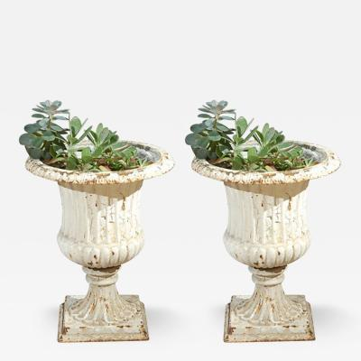 A Pair of Painted Cast Iron urns with Fluted Bodies on Pedestal Square Bases