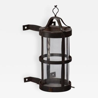 A Wrought Iron Wall Lantern by Alfred Buck with Glass Enclosure