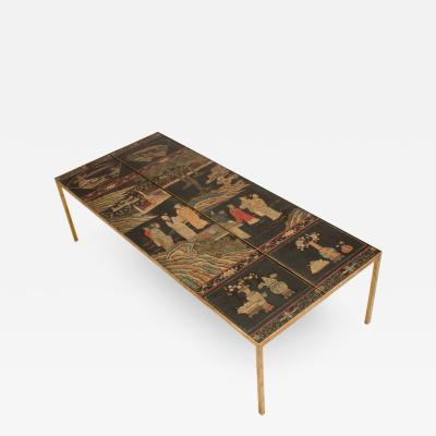 A chinoiseries top coffee table with leather trim on gilt metal base