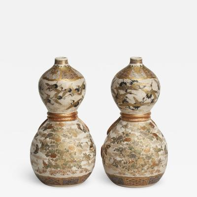 A decorative pair of Satsuma vases depicting cranes and flowers