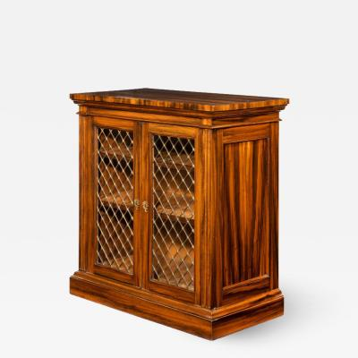 A late Regency Gon alo Alves two door side cabinet attributed to Gillows