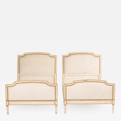 A pair of Louis XVI style painted twin beds with nail head upholstered headboard