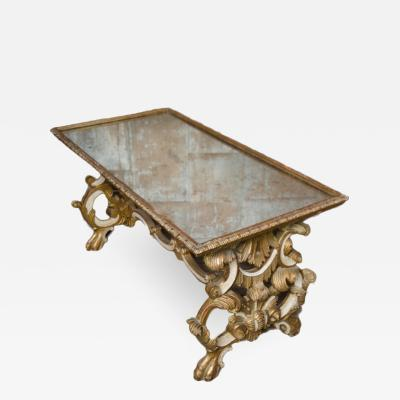A richly carved giltwood coffee table with mirrored top French 19th C