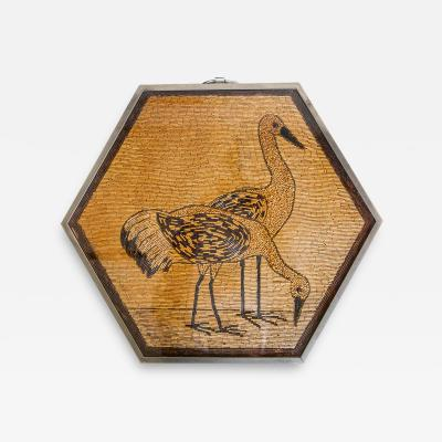 A small hexagonal folding table with a bead work image of storks