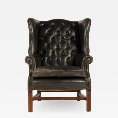 An English leather button back wing chair with mahogany frame circa 1940