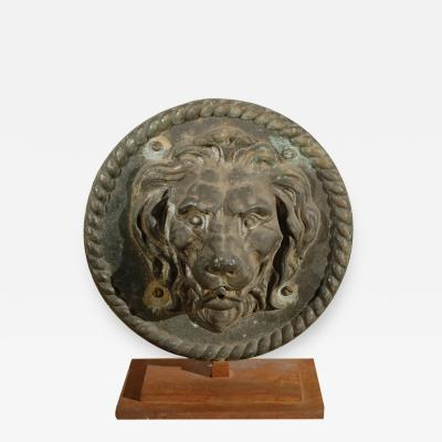 An Iron Lion Fountain Medallion Mounted on a Metal Stand