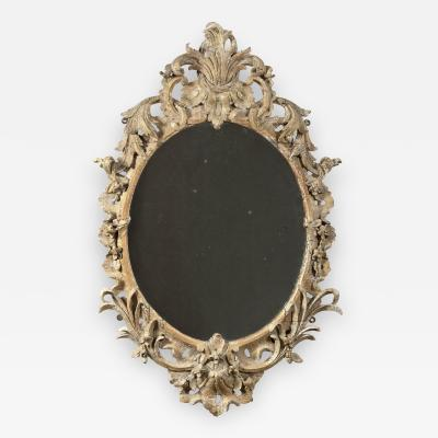 Carved and gilded and dry stripped oval mirror