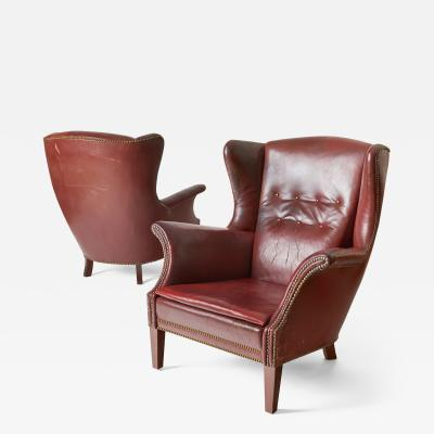 Frits Henningsen Pair of Vintage Frits Henningsen wing chairs in original leather
