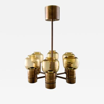 Hans Agne Jakobsson Six armed electric chandelier in brass mounted with art glass screens
