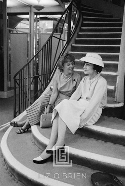 Mark Shaw Coco Chanel Sits on Stairs with Unidentified Woman
