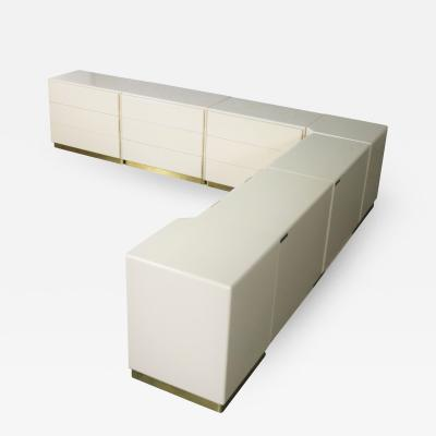 Milo Baughman Five ivory lacquered cabinets and two corner units with brass plated bases