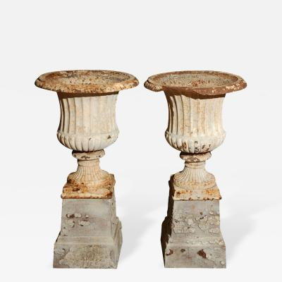 Pair of Fluted Cast Iron Urns on Plinth Bases in Remaining White Paint