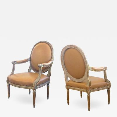 Pair of French Louis XVI Style Grey Green Painted and Parcel gilt Arm Chairs