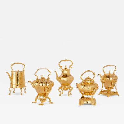 Set of five gilt kettles on conforming stands by various makers