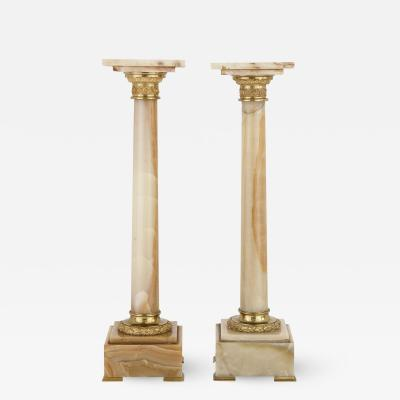 Two French white onyx and gilt bronze column shaped stands