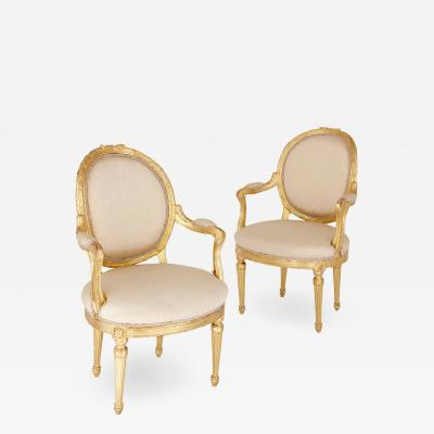 Two Louis XVI style giltwood upholstered fauteuil armchairs