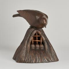 A JAPANESE CARVED WOOD OKIMONO OF A DOVE PEERING INTO A GRAIN STORE  - 1257679