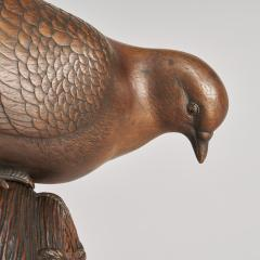 A JAPANESE CARVED WOOD OKIMONO OF A DOVE PEERING INTO A GRAIN STORE  - 1257682