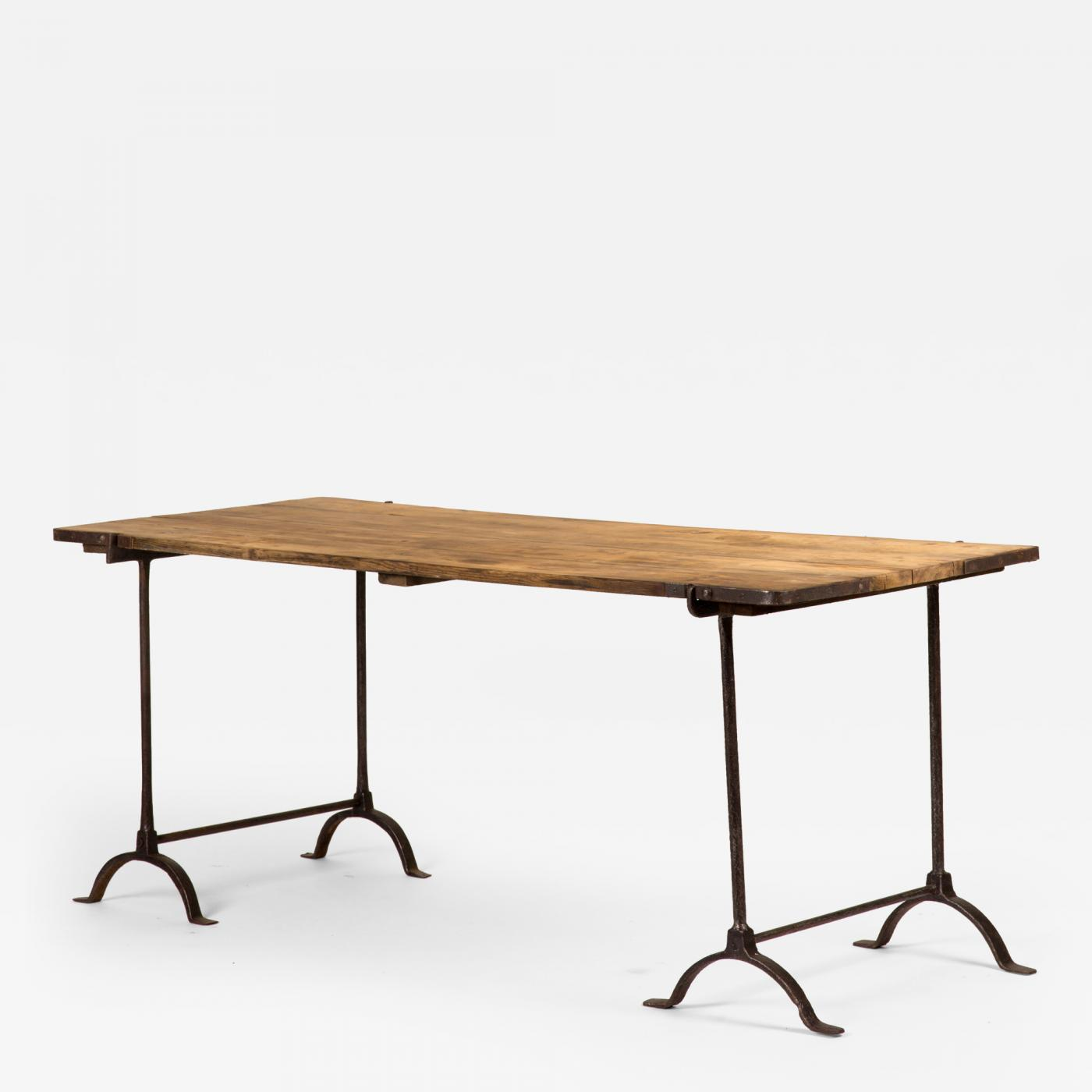A trestle table with iron base and wood top banding
